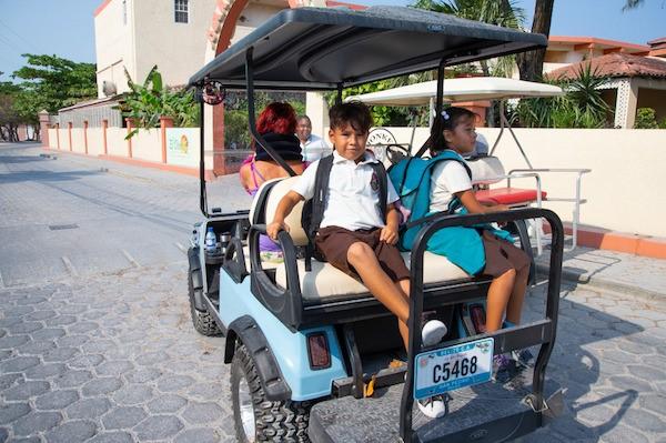 Belizean kids on a golf cart going to school