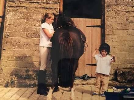 One girl, a little boy and a black horse in a stable.