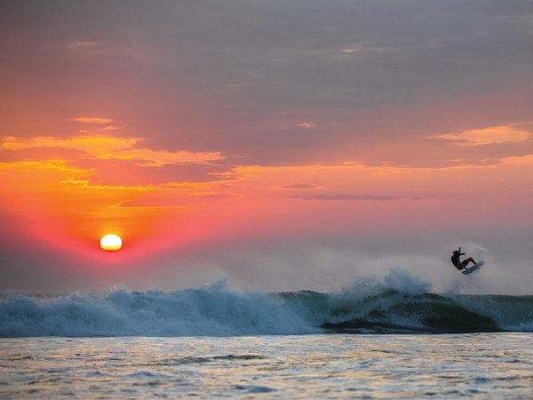 A guy surfing on the Nicaraguan sea during sunset